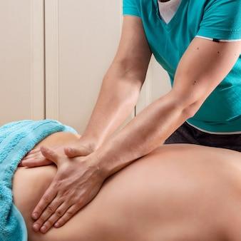 Мужчина-массажист делает антицеллюлитный массаж руками женщине, которая хочет похудеть, уход за телом и концепция оздоровления