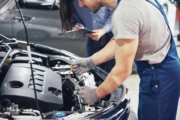 男性メカニックと女性のお客様が車のボンネットを見て、修理について話し合う