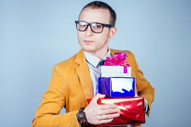 안경과 노란색 세련된 양복을 입은 괴상한 남자가 손에 선물이 든 상자를 들고 있습니다. 축하, 관대함 및 쇼핑의 개념