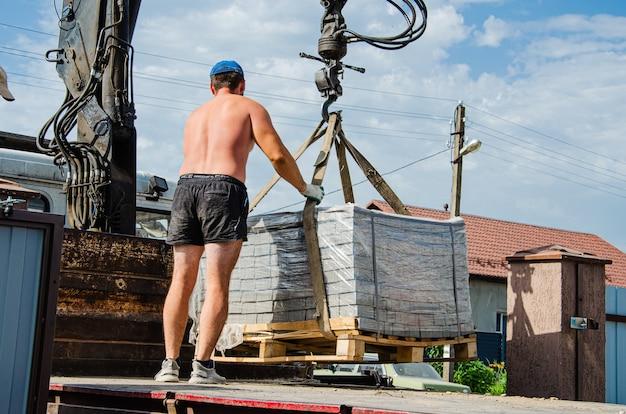 한 유럽인 남성이 차에서 타일을 땅에 싣는 일을 돕습니다. 건축 자재를 집으로 배달 및 하역. 트럭 크레인이 도로 타일을 내리지 않았습니다.