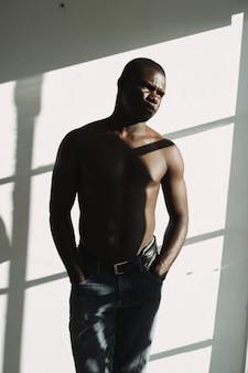 벌거 벗은 몸통이 창 근처에서 포즈를 취하는 아프리카 외모의 남자