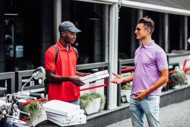 アフリカ国籍の男性がピザの配達に取り組んでいます。男はピザの配達を命じた。ピザ配達員が注文を屋外に持ち込みました。