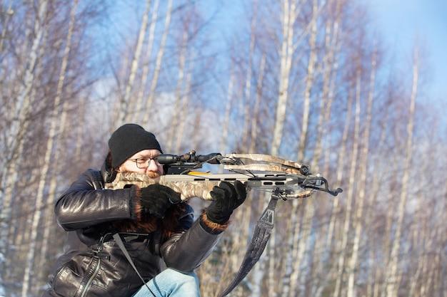 冬の森でヨーロッパの外観の男がスポーツクロスボウから撃ちます