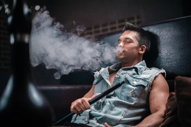 유럽 출신의 남자가 나이트 클럽에서 향기로운 동양 물 담뱃대를 피우다.