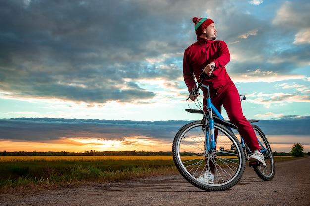 Мужчина на велосипеде на фоне заката
