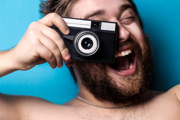 파란 벽에 남자가 손에 오래된 카메라를 들고 사진을 찍는 척하는 폭발적인 감정 프리미엄 사진