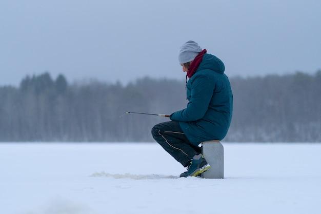 凍った雪に覆われた湖の男。側面図。冬の釣り。