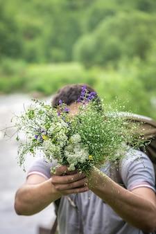 Мужчина в походе держит букет полевых цветов на размытом фоне.