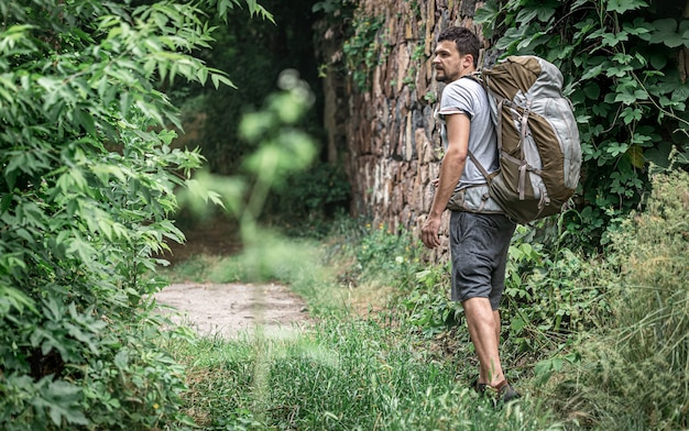 큰 배낭을 메고 하이킹을 하는 남자가 숲을 여행합니다.