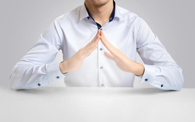 テーブルで白いシャツを着た明るい背景の男