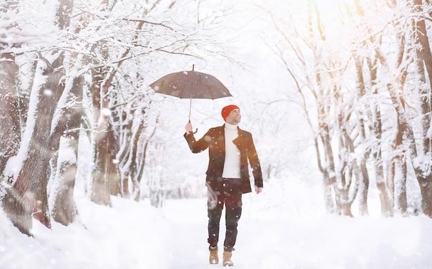 공원에서 산책에 남자입니다. 겨울 강설량 아래 우산을 든 젊은 남자.