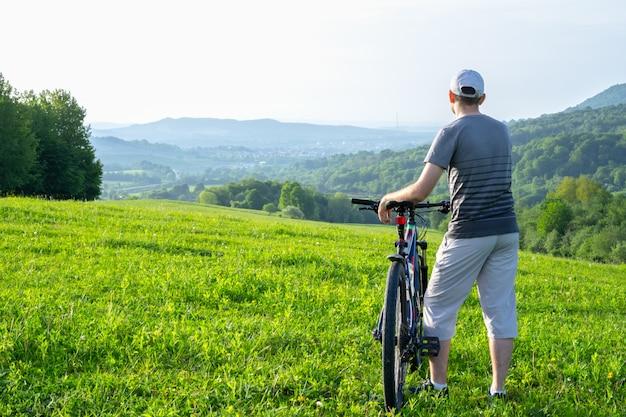 自転車に乗った男が遠くを覗く
