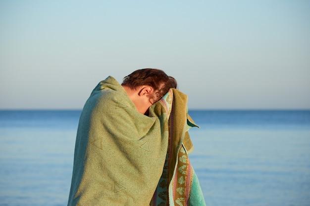 수건으로 몸을 말리는 해변의 남자