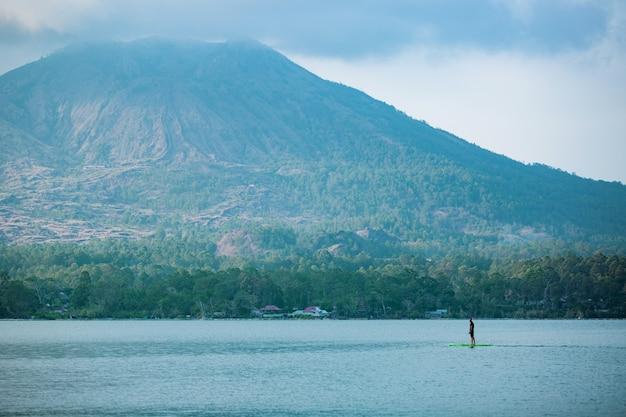 湖の男がサップボードに乗る。