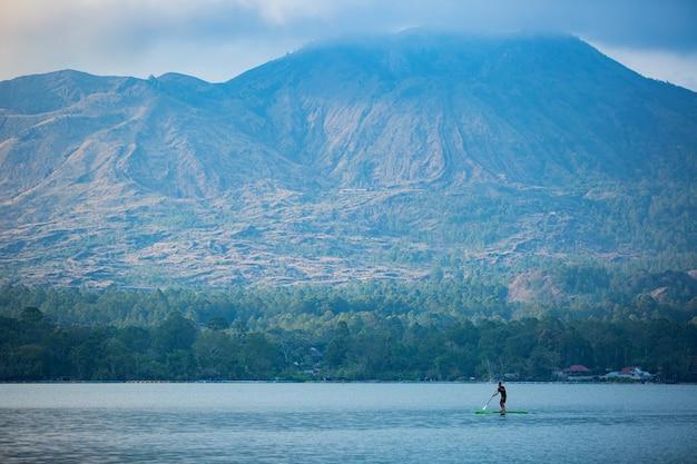 Мужчина на озере катается на доске. Бесплатные Фотографии