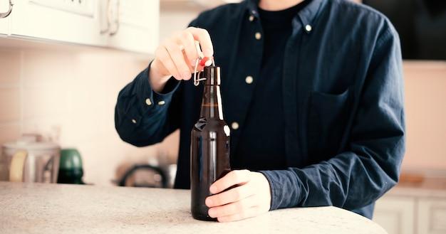 남자는 파티 나쁜 습관 알코올 중독자에 유리 맥주 병을 엽니 다