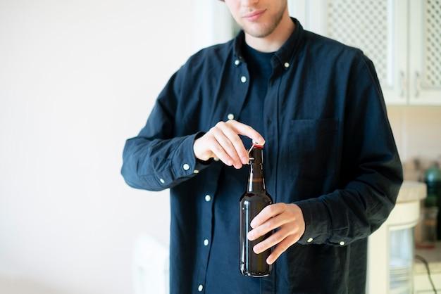 男はパーティーでガラスのビール瓶を開ける、悪い習慣、アルコール中毒者