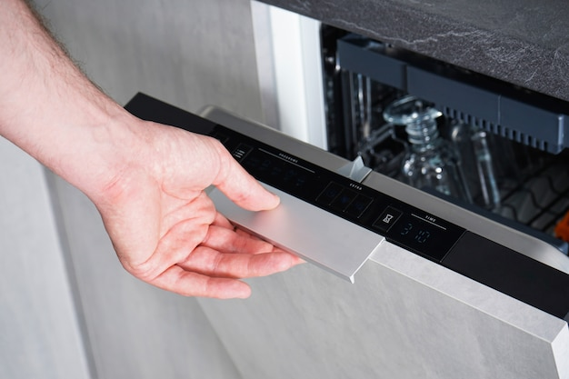 食器洗い機を開閉する男性