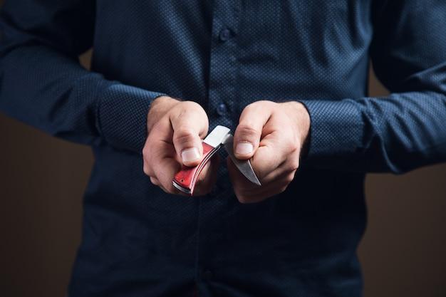 Мужчина открывает ручной нож на коричневой поверхности