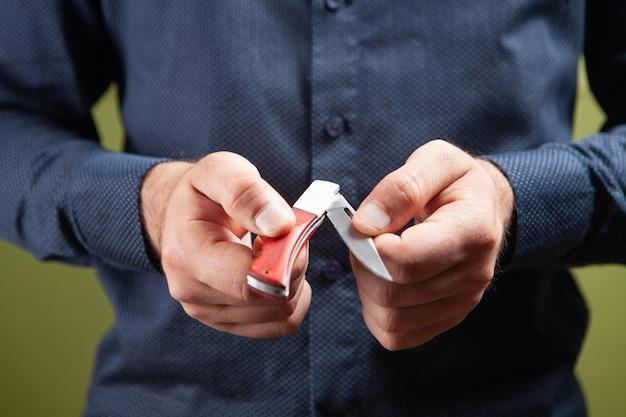 Мужчина открывает ручной нож на зеленом фоне
