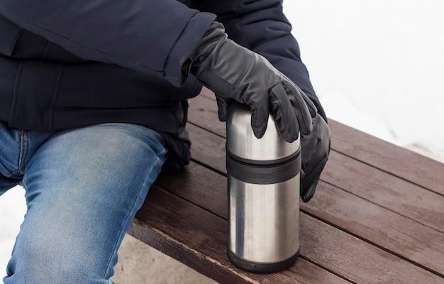 한 남자가 겨울에 따뜻한 커피 보온병을 열어 보온을 유지합니다.