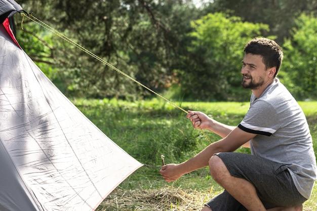 テントを張る途中の屋外の男。