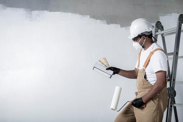 한 남자가 롤러로 흰 벽을 그립니다. 인테리어 수리. 빈 방에 벽을 그리는 젊은 남성 장식가, 컨셉 빌더 또는 빈 방 위에 페인트 롤러가 달린 헬멧을 쓴 화가.