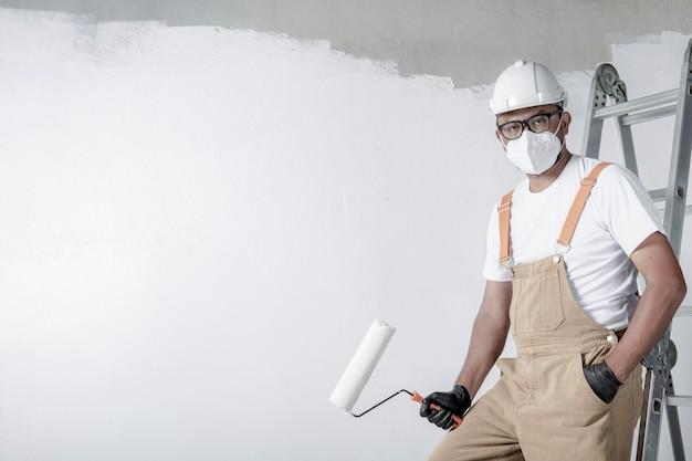 한 남자가 롤러로 흰 벽을 그립니다. 인테리어 수리.