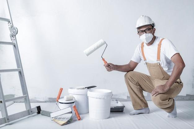 남자는 내부의 롤러 수리로 흰 벽을 칠한다