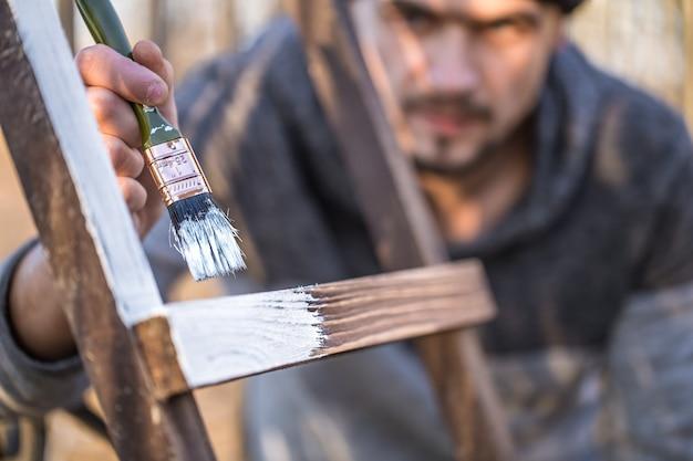 男は木の板に白いペンキでペイントします。産業概念の男。テキストのための場所があり、オブジェクトがクローズアップ
