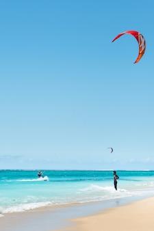 モーリシャス島のインド洋、モーリシャスのルモーンビーチでパラグライダーをする男性