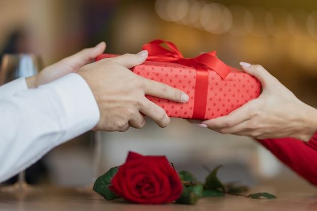 男は、赤いリボンが付いたプレゼントのギフトボックスをガールフレンドに渡します。 。レストランの暖かくて素敵な背景。カフェのテーブルにグラス2杯のワインとバラ。バレンタインデーのコンセプト。