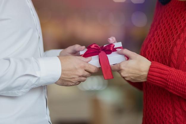男は彼のガールフレンドの手に赤いリボンで白いプレゼントギフトボックスを渡します。カップルのクラシックな外観、赤いセーターと白いシャツ。バレンタインデーと冬の休日のコンセプト。