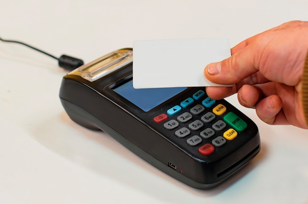 Мужчина платит на кассе кредитной картой через беспроводной платежный терминал.