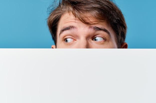 Мужчина выглядывает из-за рекламного баннера copy space крупным планом