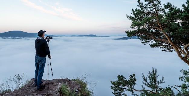 Мужчина-фотограф в горах фотографирует фотоаппаратом на штативе природу и утро ...