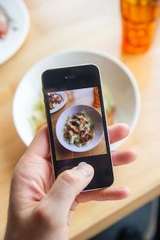 한 남자가 레스토랑에서 휴대전화로 맛있는 샐러드 사진을 찍고 있다