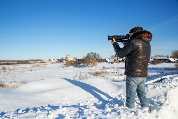 男が冬の風景を撮影