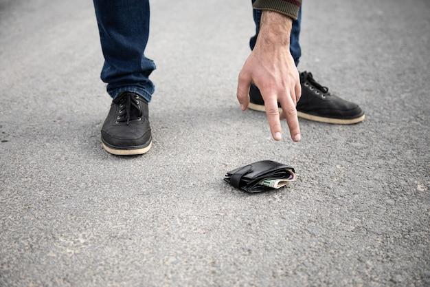 Мужчина поднимает бумажник с асфальта