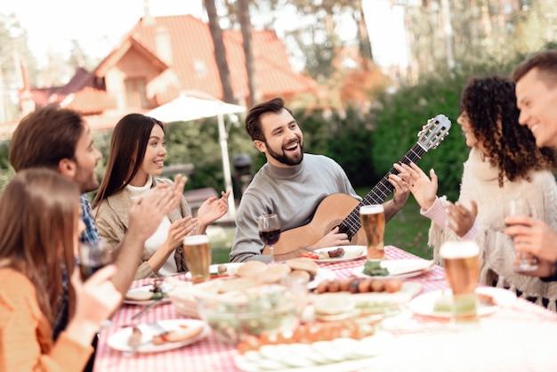 Мужчина играет на гитаре во время пикника с друзьями.
