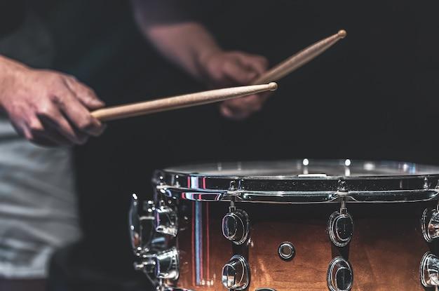 男は棒でスネアドラムを演奏し、ドラマーは打楽器を演奏し、クローズアップします。