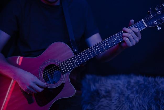 男は暗い部屋のコピースペースでアコースティックギターを弾きます。ライブパフォーマンス、アコースティックコンサート。