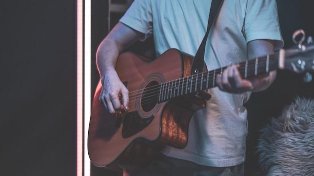 한 남자가 어두운 방에서 어쿠스틱 기타를 연주합니다. 라이브 공연, 어쿠스틱 콘서트, 연습.