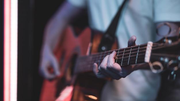 Мужчина играет на акустической гитаре в темной комнате. живое выступление, акустический концерт.
