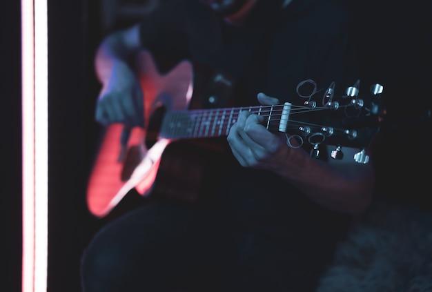 한 남자가 어두운 방에서 어쿠스틱 기타를 연주합니다. 라이브 공연, 어쿠스틱 콘서트.