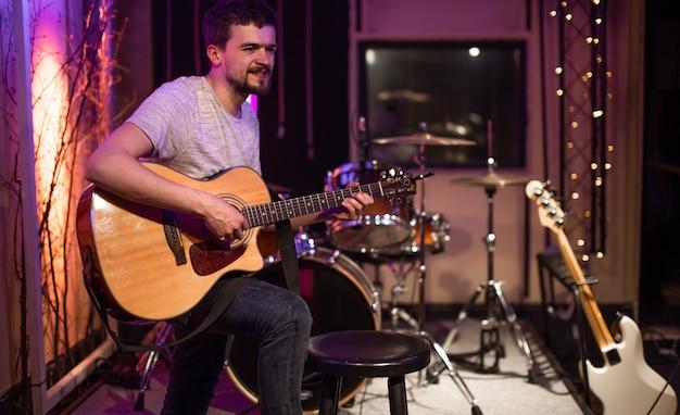 한 남자가 녹음 스튜디오에서 어쿠스틱 기타를 연주합니다. 테이블에 드럼 키트가있는 뮤지션 리허설을위한 공간입니다. 음악적 창의성과 쇼 비즈니스의 개념.