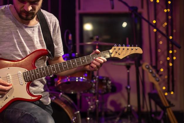 한 남자가 녹음 스튜디오에서 일렉트릭 기타를 연주합니다. 테이블에 드럼 키트가있는 뮤지션을위한 리허설 룸. 음악적 창의성의 개념.