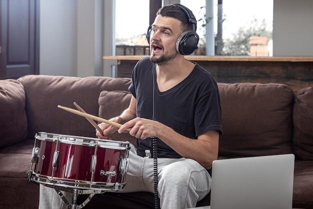 한 남자가 드럼을 연주하고 노트북 화면을 봅니다. 온라인 음악 수업, 화상 회의 수업의 개념.