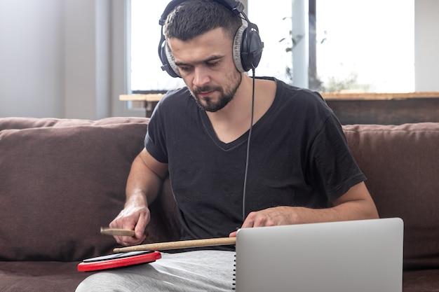 男がドラムを演奏し、ノートパソコンの画面を見ます。オンライン音楽レッスン、ビデオ会議レッスンの概念。