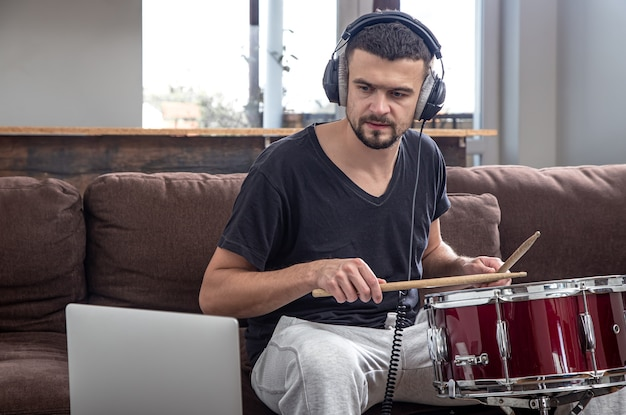 Мужчина играет в барабан и смотрит на экран ноутбука. концепция онлайн-уроков музыки, уроков по видеоконференцсвязи.